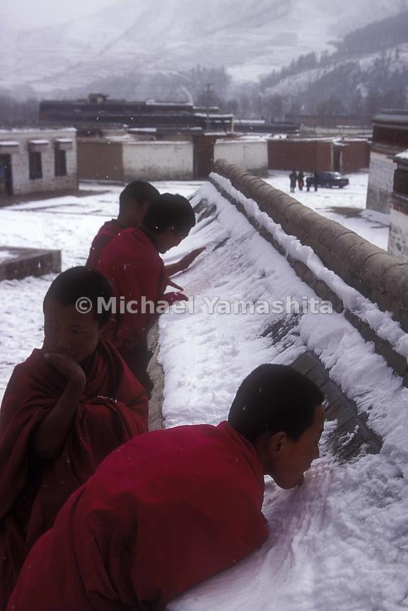 Monks quench their thirst with freshly fallen snow.