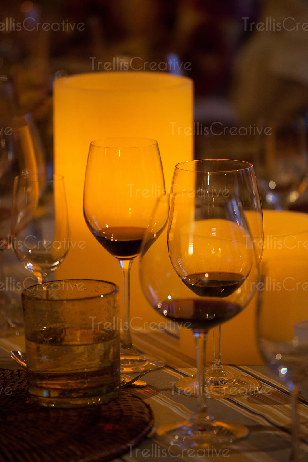 Glowing candlelit table with wine glasses