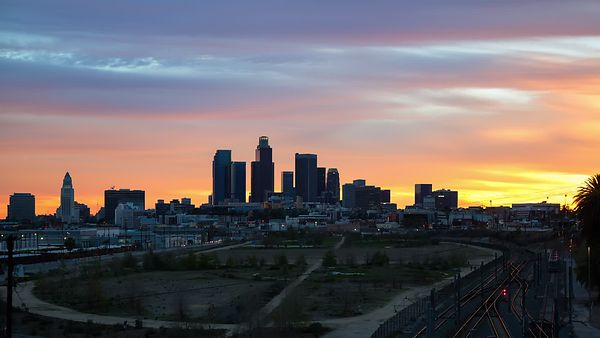 Wide Shot: Beautiful Fiery Pastel Sunset Over Los Angeles Skyline & Busy State Park (Day To Night)