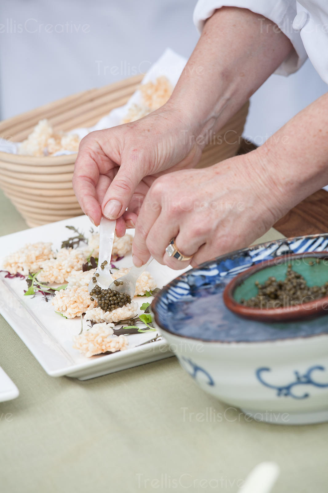 A female chef places black caviar on a puffed rice cracker
