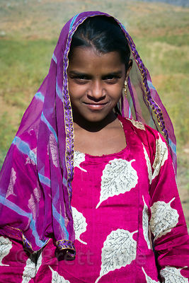 Goat herding girl in a striking pink outfit, Kharekhari village, Rajasthan, India