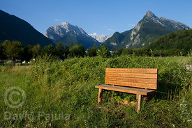 Wood bench (with Psalm 24,1 : 67,4 inscription) near Bovec with Svinjak Mountain on the background (right)