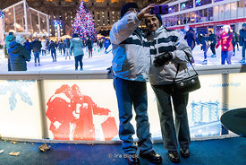 Tourists taking selfies against the backdrop of people skating on the ice rink at Bryant Park Winter Village in Manhattan, New York