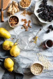Ingredients on marble surface. Pears, blackberries, honey, nuts, ginger and oats.