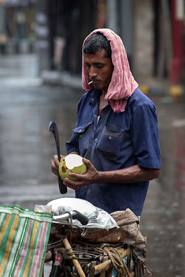 A man makes juices in monsoon rains, Lake Gardens, Kolkata, India