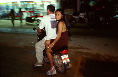A Western man drives a bar girl on a motorcycle