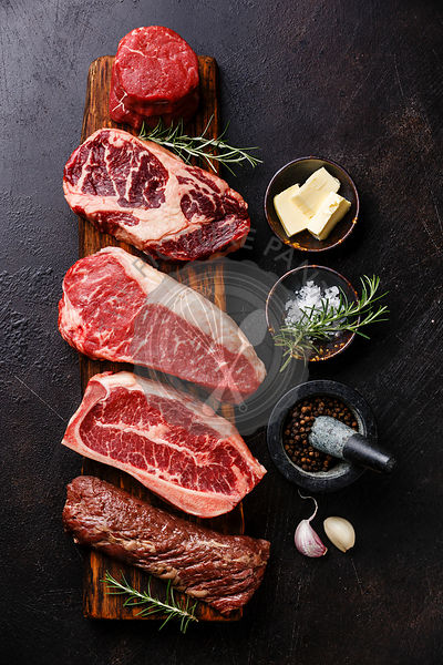 Variety of Raw Black Angus Prime meat steaks Machete, Blade on bone, Striploin, Rib eye, Tenderloin fillet mignon on wooden board and seasoning