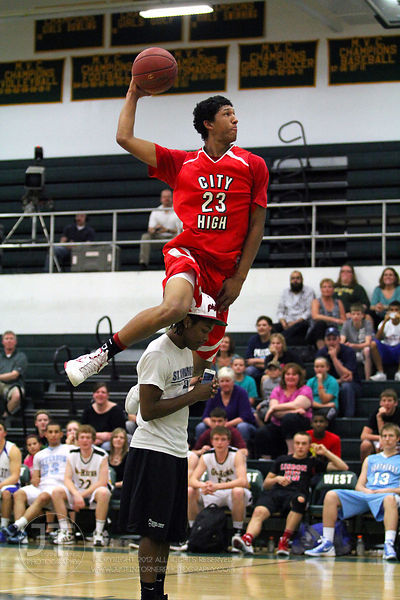 Iowa CIty High's Jerel Moore jumps over Richard Bryant of Iowa City West High in the slam dunk competition. The Northern All-Star team defeated the Southern All-Star team 73-70 Wednesday night in Iowa CIty. (Justin Torner/Freelance)