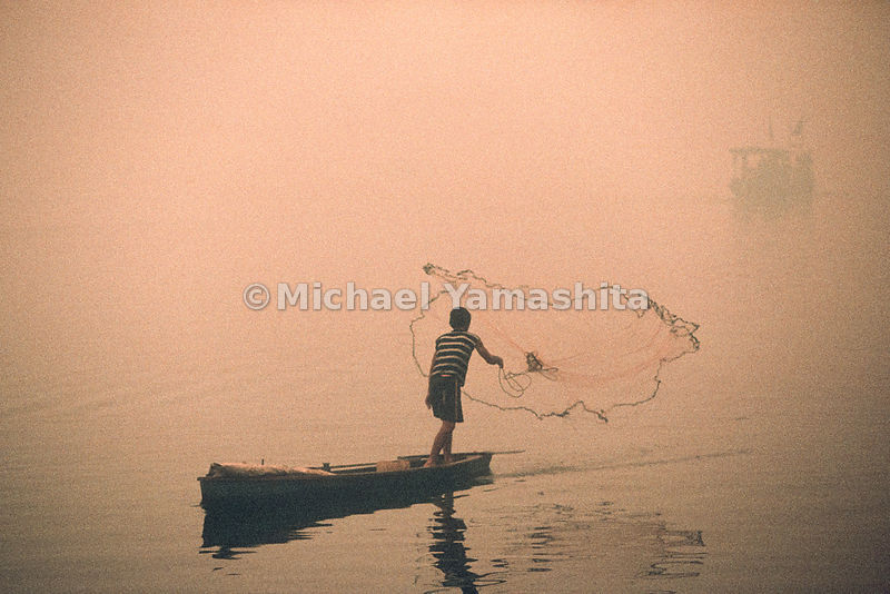 From his canoe, a fisherman casts out his net to make a large catch.