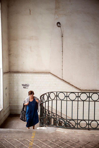 A woman climbs the stairs at the Mercado do Bolhão, Porto, Portugal.