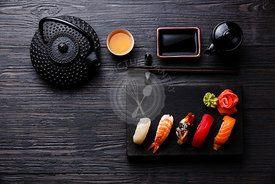 Nigiri Sushi set on wooden serving board and Green tea on black wooden background