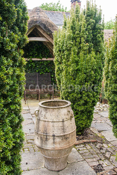 Large pithoi framed by four yews, Taxus baccata Aurea Group in the Thatched Garden. Caervallack Farm, St Martin, Helston, Cornwall, UK