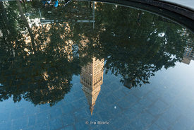 The Met Life Tower reflected in a pond in Madison Square Park. This landmark New York City skyscraper was opened in 1909, and its 50 floors made it the tallest building in the world until 1913. It has recently been converted into the New York Edition Hotel.