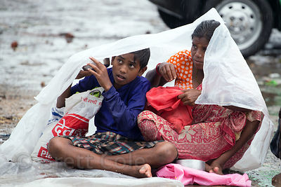A woman and her son huddle under a piece of plastic during monsoon rains while panhandling, Babughat, Kolkata, India