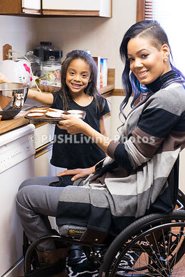 Young mother in a wheelchair cooking with her daughter