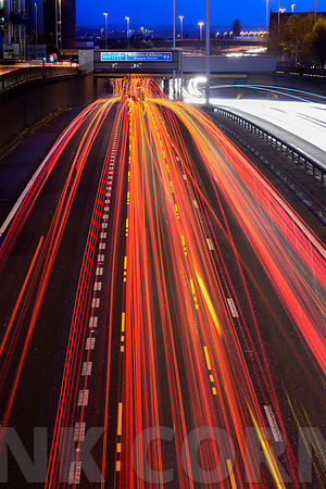 GLASGOW, SCOTLAND – NOVEMBER 30, 2015: Streaks of coloured light from vehicles travelling during a winter rush hour on the M8 motorway in Glasgow.
