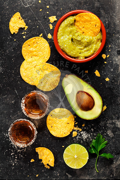 Bowl of mexican nachos chips with homemade fresh guacomole sauce and tequila shots over old  background. Top view. With space for text