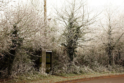 Frozen telephone kiosk in a country lane