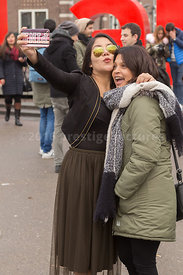Two young women taking a selfie by the I AMsterdam at museumplein
