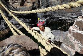 Man ties rope to one of the main foundation ropes once it is in position so it can be tensioned, Q'eswachaka , Canas province , Peru