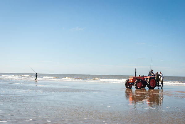 Red tractor on the shore