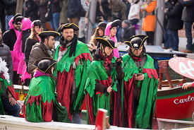 Men & Women in Green and Scarlet CLoaks in the Venice Carnival Water Parade  on the Rio di Cannaregio Canal