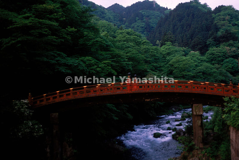 A red bridge contrasting against green mountains seems to offer magical entry into the beyond.