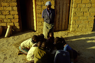Burundi - Ruyigi - A neighbour keeps an eye on the child-headed household in a village built by Maggy