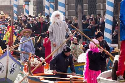 Man with a white hair and beard wig in the Venice Carnival Water Parade on the Rio di Cannaregio Canal