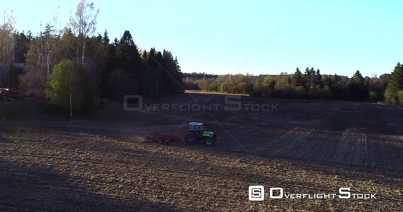 Spring Plowing, Aerial View Around a Plow Machine Sowing, Sunny Spring Evening Dawn, Uusimaa, South Finland
