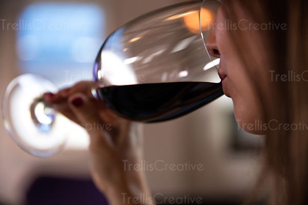 Close-up of a woman drinking red wine in a glass