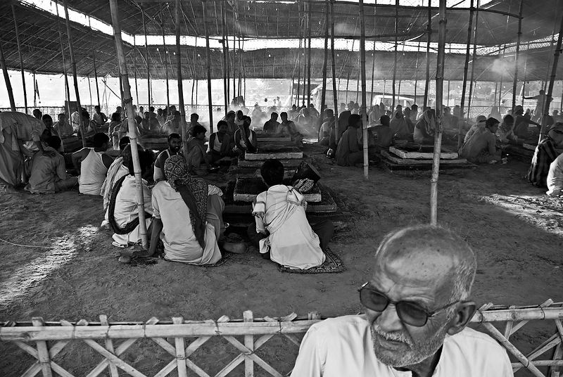 This portrait of an old man was shot during the Kumbh Mela. In the background the pilgrims wait for the Havan ceremony to start.