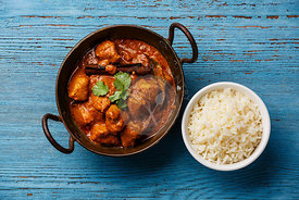 Chicken tikka masala spicy curry meat food and basmati rice on blue wooden background