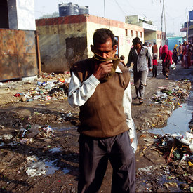A man covers his mouth as he crosses the open sewers in a main street of Kathputli Colony
