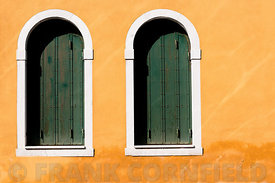 Windows with closed shutters in building in Venice.