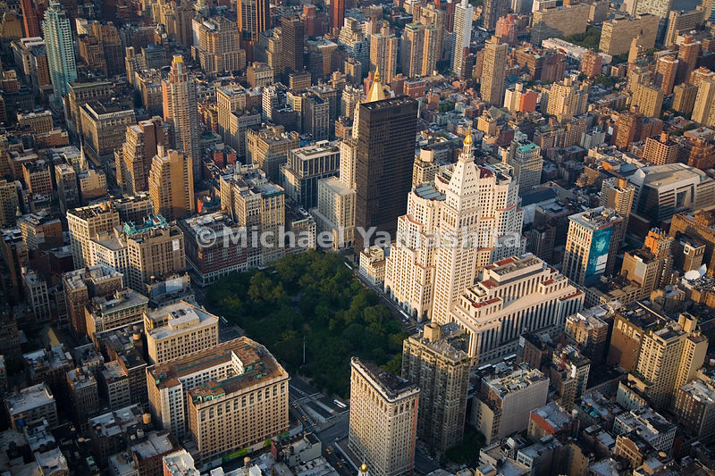The bottom part of the photo shows the south edge of Madison Square Park, the former site of Madison Square Garden, with the towering triangular Flatiron Building.  Manhattan, New York City.