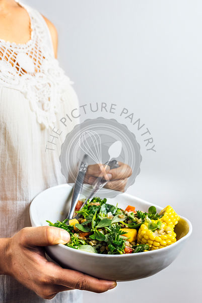 A woman with a white summer top is holding a bowl of refreshing lentil salad with herbs, peaches and corn.