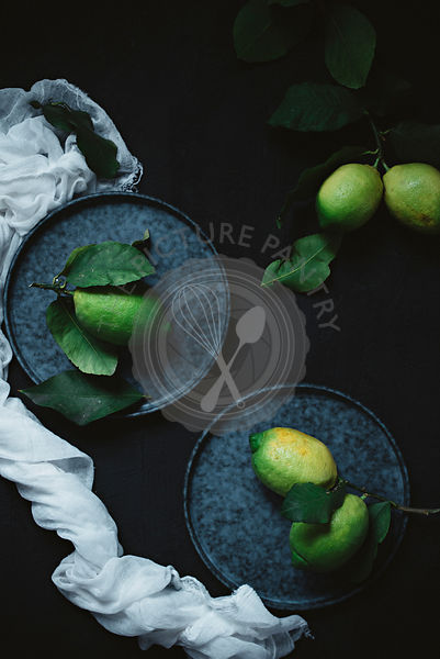 Unripe lemons on a dark background