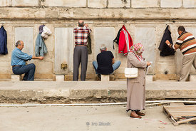 Turkish men washing their feet before entering the New Mosque, The Yeni Cami, or Mosque of the Valide Sultan in Istanbul.