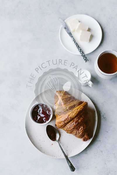 Croissant and jam on hite background