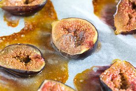 oven roasted brown figs on baking paper showing drizzled honey