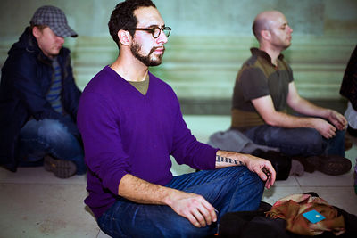 UK - London - Men taking part in a meditation flash mob in the Great Court of the British Museum