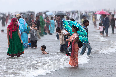 Families recreate in the Arabian Sea during monsoon rains at Juhu Beach, Mumbai, India. Juhu is a popular family destination on weekend afternoons.