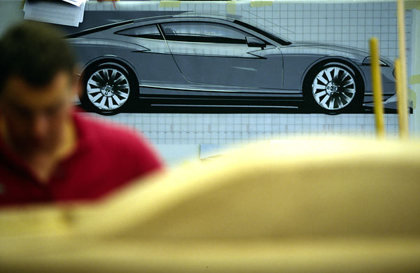 UK - Coventry - A worker shapes a clay model of a new Jaguar car