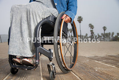 Woman in a wheelchair on a coastal boardwalk