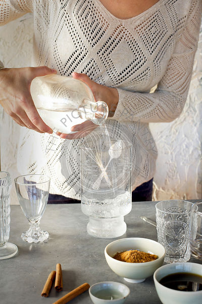 A Women is pouring Sparkling Water into glassware. Photographed on dark gray background.