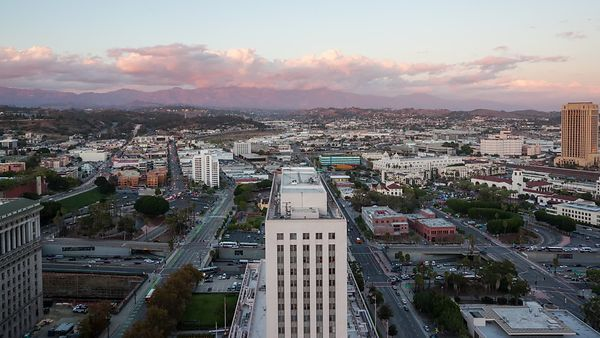 Bird's Eye: Tight Shot of Pretty Clouds Over Government Building, City Traffic, China Town, & the San Gabriel Mountain Range