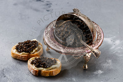 Black caviar in silver bowl and sandwiches on gray concrete background
