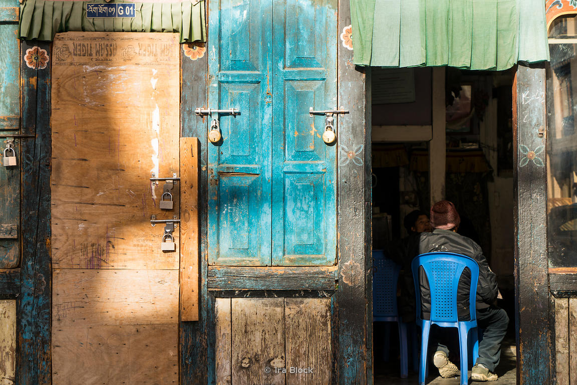 Wooden doors with locks and a man stting on a chair in Thimphu, Bhutan.