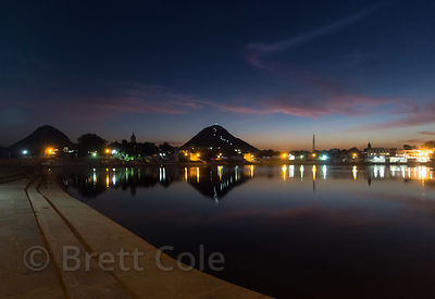 Sunset reflecting in Pushkar Lake, with Savitri mountain and temple in the distance, Pushkar, Rajasthan, India